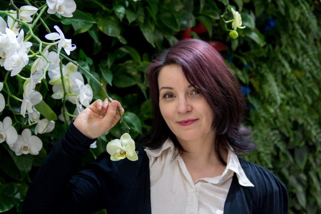Kuvassa Sanna Seesvalo pitää kädessään valkoista orkideaa viherseinätaustaa vasten.